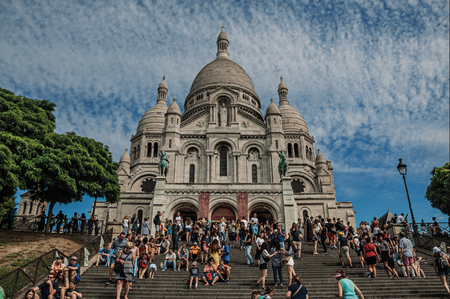 """Paris, France - July 08, 2017. People, staircase and Basilica of Sacre Coeur facade in Paris. Known as the """"City of Light"""", it is one of the most impressive cultural centers in the world. Northern France."""
