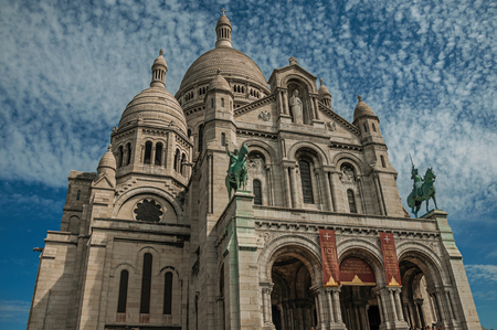 Paris, France - July 08, 2017. Cloudy blue sky and Basilica of Sacre Coeur facade in Paris. Known as the