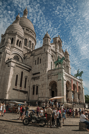 """Paris, France - July 08, 2017. People, blue sky and Basilica of the Sacre Coeur facade in Paris. Known as the """"City of Light"""", it is one of the most impressive cultural centers in the world. Northern France. Editorial"""