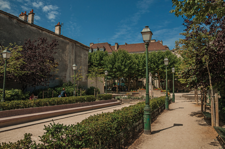 Paris, northern France - July 08, 2017. Wooded gardens and apartment buildings under sunny blue sky at Montmartre in Paris. Known as one of the world's most impressive cultural centers.