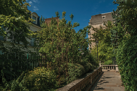 Sidewalk in wooded gardens of condos under sunny blue sky at Montmartre in Paris. Known as the