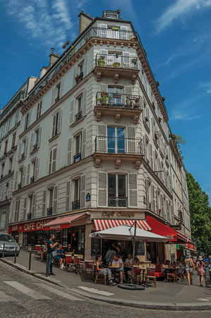 Paris, France - July 08, 2017. People having fun in Montmartres restaurant in sunny day at Paris. Known as the City of Light, it is one of the most impressive cultural centers in the world. Northern France.