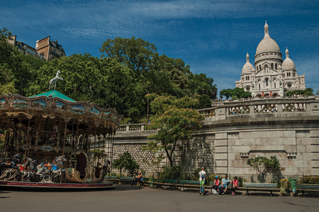 """Paris, France - July 08, 2017. People, carousel and Sacre Coeur Basilica at Montmartre in Paris. Known as the """"City of Light"""", it is one of the most impressive cultural centers in the world. Northern France"""