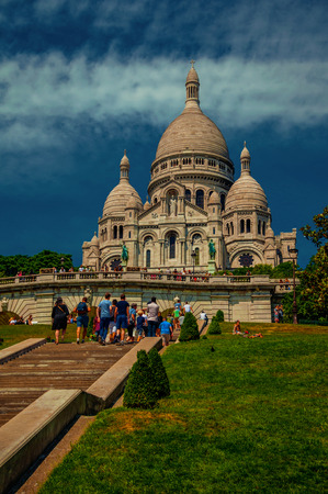 """Garden with people, lawn and staircase in front Basilica of Sacre Coeur at Montmartre in Paris. Known as the """"City of Light"""", it is one of the world's most awesome cultural centers. Northern France. Imagens"""