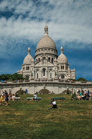 """Paris, France - July 08, 2017. People, lawn and Basilica of the Sacre Coeur at Montmartre in Paris. Known as the """"City of Light"""", it is one of the world's most awesome cultural centers. Northern France. Editorial"""