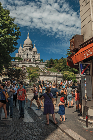 """Paris, France - July 08, 2017. People on street and Basilica of Sacre Coeur at Montmartre in Paris. Known as the """"City of Light"""", it is one of the world's most awesome cultural centers. Northern France."""