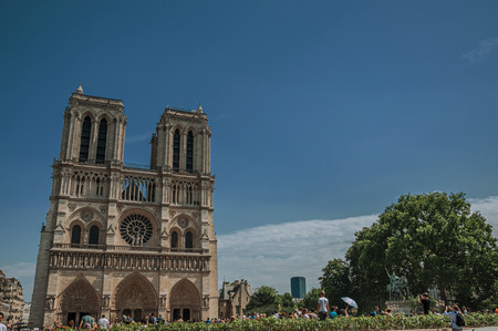 """Paris, France - July 08, 2017. People and gothic Notre-Dame Cathedral at Paris City Center. Known as the """"City of Light"""", it is one of the world's most awesome cultural centers. Northern France."""