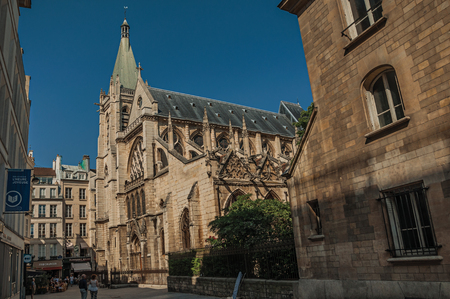 """Paris, France - July 08, 2017. People, gothic church on an alley and sunny blue sky in Paris. Known as the """"City of Light"""", it is one of the most impressive cultural centers in the world. Northern France."""
