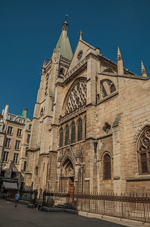 """Paris, France - July 08, 2017. People, gothic church on an alley and sunny blue sky in Paris. Known as the """"City of Light"""", it is one of the most impressive cultural centers in the world. Northern France. Editorial"""