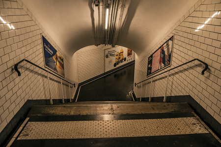 Paris, northern France - July 09, 2017. Advertising and stairs in passageway linking stations of the Paris Subway. Known as the