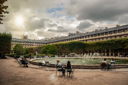 Paris, northern France - July 10, 2017. Buildings, garden fountain with people and sunlight at the Palais-Royal in Paris. Known as one of the world's most impressive cultural centers. Retouched photo Editorial