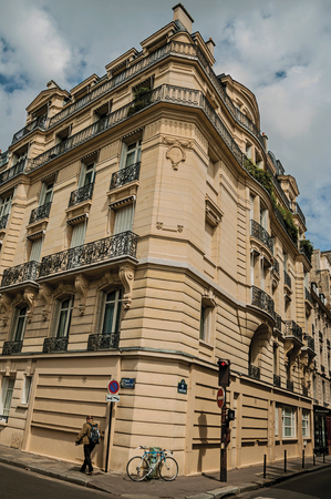 """Paris, France - July 11, 2017. Man walking on street corner and building in typical Paris style. Known as the """"City of Light"""", it is one of the most impressive cultural centers in the world. Northern France. Editorial"""