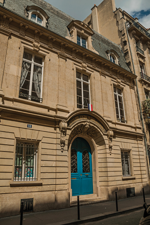 Paris, northern France - July 11, 2017. Facade of old building with decorated door and windows in a sunny day at Paris. Known as one of the world's most impressive cultural centers. Editorial