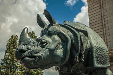 """Paris, northern France - July 11, 2017. Sculpture of rhino in front of building in the sunny day at Paris. Known as the """"City of Light"""", it is one of the world's most awesome cultural centers."""