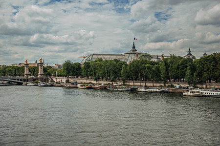 """Boats at Seine River, Alexandre III bridge and Grand Palais building in the background in Paris. Known as the """"City of Light"""", it is one of the most impressive cultural centers in the world. Northern France."""
