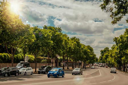 Paris, France - July 11, 2017. Cars on a tree-lined street in sunny day at Paris. Known as the City of Light, it is one of the most impressive cultural centers in the world. Northern France. Retouched photo. Editorial