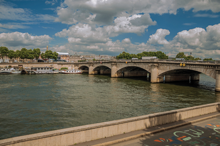 Boats anchored at the Seine River bank with trees and bridge under the sunny blue sky in Paris. Known as the City of Light, it is one of the most impressive cultural centers in the world. Northern France.