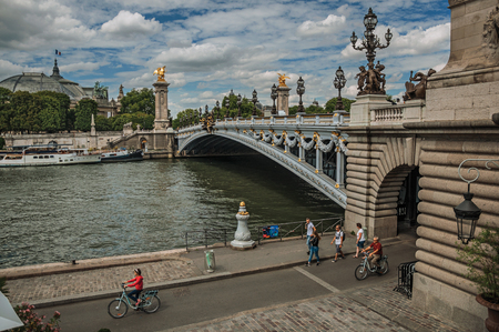 Paris, France - July 11, 2017. Alexandre III bridge and people at Seine River bank in Paris. Known as the