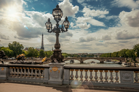 Golden statue and lighting post adorning the Alexandre III bridge over the Seine River and Eiffel Tower in Paris. Known as one of the worlds most impressive cultural centers. Retouched photo.