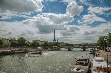 Eiffel Tower, bridge and boats anchored at Seine River bank on sunny day in Paris. Known as the