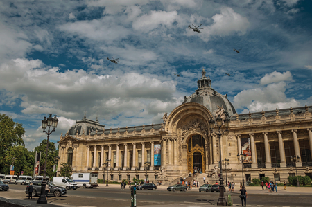 """Paris, France - July 11, 2017. Helicopters passing by the Petit Palais on sunny day in Paris. Known as the """"City of Light"""", it is one of the most impressive cultural centers in the world. Northern France."""