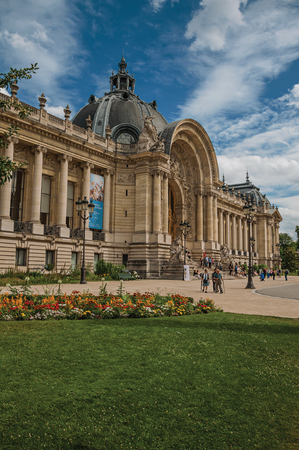 """Paris, France - July 11, 2017. People and garden in front of the Petit Palais's facade in Paris. Known as the """"City of Light"""", it is one of the most impressive cultural centers in the world. Northern France."""