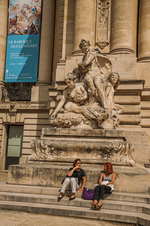 Paris, France - July 11, 2017. People sit on steps under statue at the Petit Palais in Paris. Known as the