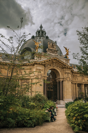 Paris, France - July 11, 2017. People sitting on benches at the Petit Palais courtyard in Paris. Known as the Editorial