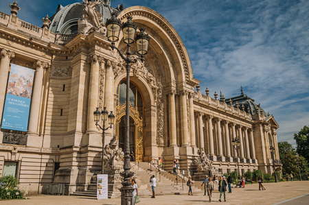 """Paris, France - July 11, 2017. People and staircase at the Golden Gate of Petit Palais at Paris. Known as the """"City of Light"""", it is one of the most impressive cultural centers in the world. Northern France."""