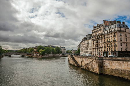 Old buildings, wall on the banks of the Seine River and bridges with cloudy sky in Paris. Known as the