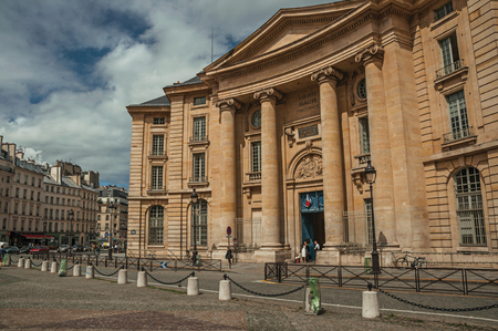 Paris, northern France - July 12, 2017. People in front Neoclassical building, cobblestone and cloudy sky in Paris. Known as the