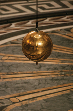 Paris, northern France - July 12, 2017. Close-up of the famous Foucault Pendulum copper ball swinging inside the Pantheon in Paris. Known as one of the world's most impressive cultural centers. Editorial