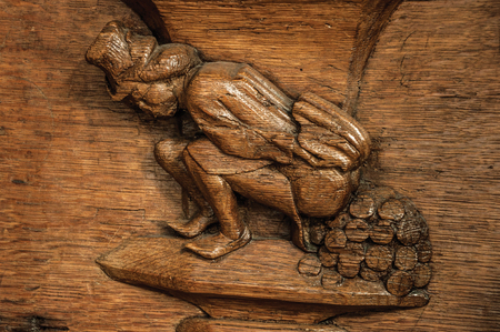 """Amsterdam, northern Netherlands, June 27, 2017. Weird high relief wooden sculpture of man """"pooping coins"""" in old church of Amsterdam. Famous for its huge cultural activity, graceful canals and bridges"""