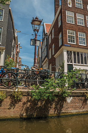 Amsterdam, northern Netherlands - June 27, 2017. Bicycles stuck in light post and balustrade next to canal at Amsterdam. Famous for its huge cultural activity, graceful canals and bridges. Editorial