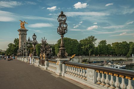 """Paris, France - July 07, 2017. People on elegant Alexandre III bridge over the Seine River in Paris. Known as the """"City of Light"""", it is one of the world's most awesome cultural centers. Northern France. Editorial"""