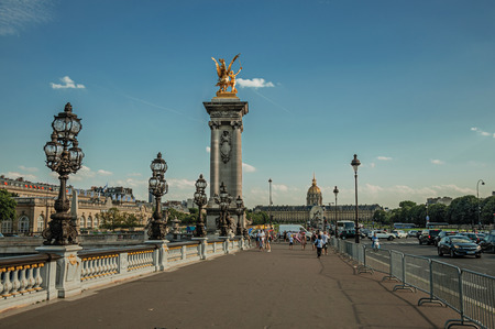 Paris, France - July 07, 2017. People on elegant Alexandre III bridge over the Seine River in Paris. Known as the City of Light, it is one of the worlds most awesome cultural centers. Northern France.