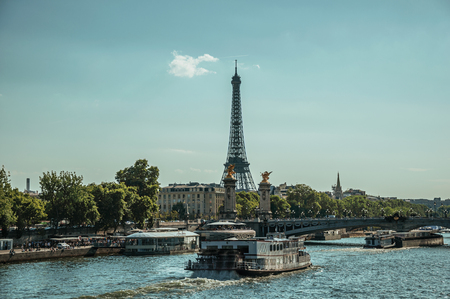 """Paris, France - July 07, 2017. Boat on the Seine River, bridge and Eiffel Tower at sunset in Paris. Known as the """"City of Light"""", it is one of the world's most awesome cultural centers. Northern France. Editorial"""
