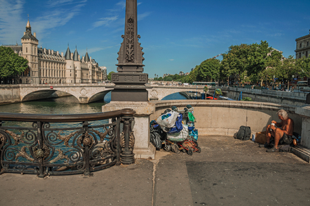 """Paris, France - July 08, 2017. Beggar on bridge over the Seine River with sunny blue sky in Paris. Known as the """"City of Light"""", it is one of the most impressive cultural centers in the world. Northern France."""