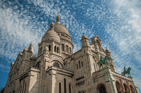 """Paris, France - July 08, 2017. Cloudy blue sky and Basilica of Sacre Coeur facade in Paris. Known as the """"City of Light"""", it is one of the most impressive cultural centers in the world. Northern France."""