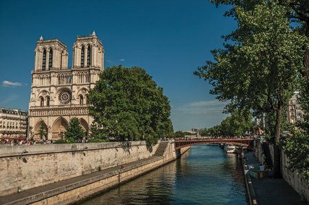 """Paris, France - July 08, 2017. People, Seine River and gothic Notre-Dame Cathedral at Paris. Known as the """"City of Light"""", it is one of the world's most awesome cultural centers. Northern France."""