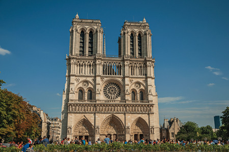 """Paris, France - July 08, 2017. People and gardens at the gothic Notre-Dame Cathedral in Paris. Known as the """"City of Light"""", it is one of the world's most awesome cultural centers. Northern France. Editorial"""