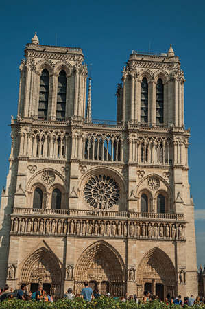 """Paris, France - July 08, 2017. People and gardens at the gothic Notre-Dame Cathedral in Paris. Known as the """"City of Light"""", it is one of the world's most awesome cultural centers. Northern France."""
