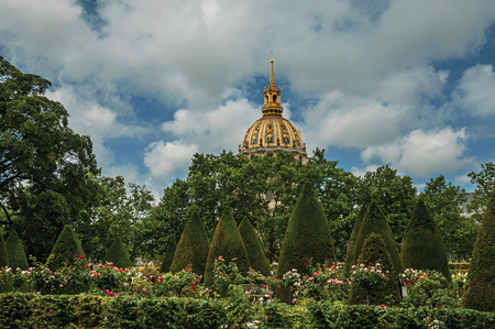 """Paris, northern France - July 11, 2017. Rodin Museum garden and Les Invalides golden dome in cloudy day at Paris. Known as the """"City of Light"""", it is one of the most impressive cultural centers in the world."""
