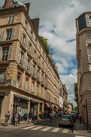 """Paris, France - July 11, 2017. Buildings and people walking down the street in sunny day at Paris. Known as the """"City of Light"""", it is one of the most impressive cultural centers in the world. Northern France."""