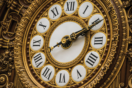 """Paris, northern France - July 11, 2017. Close-up of golden clock at the Quai d'Orsay Museum main hall in Paris. Known as the """"City of Light"""", it is one of the world's most awesome cultural centers."""