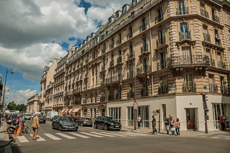 """Paris, France - July 11, 2017. Buildings and people walking down the street in sunny day at Paris. Known as the """"City of Light"""", it is one of the most impressive cultural centers in the world. Northern France. Editorial"""