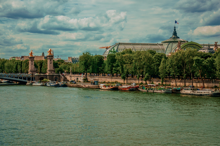 """Boats at Seine River, Alexandre III bridge and Grand Palais building in Paris. Known as the """"City of Light"""", it is one of the most impressive cultural centers in the world. Northern France. Retouched photo"""