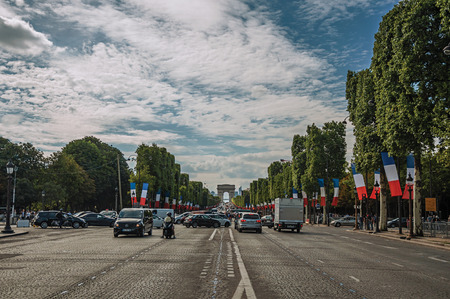 Paris, France - July 11, 2017. Trees and cars on the bustling Champs-Elysees Avenue in Paris. Known as the