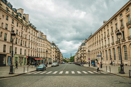 Paris, northern France - July 12, 2017. Old buildings and people on a cobblestone avenue on cloudy sky in Paris. Known as the