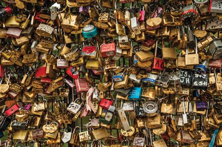Paris, northern France - July 12, 2017. Padlocks fastened to each other celebrating love on bridge balustrade at Seine River in Paris. Known as one of the world's most impressive cultural centers.
